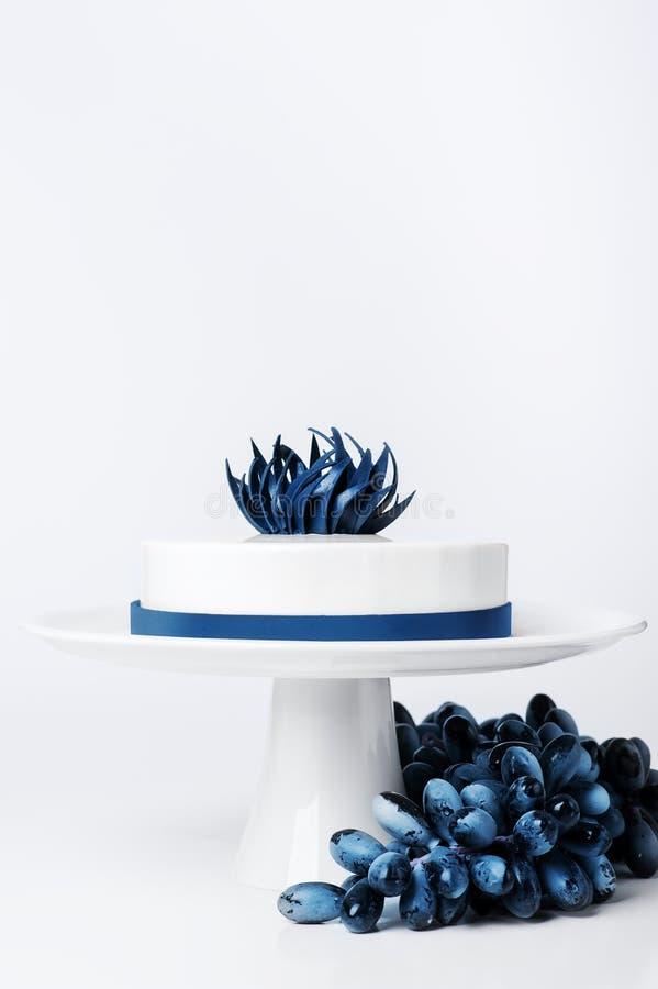 Il dolce bianco d'avanguardia moderno di nozze sul supporto del dolce ha isolato il fondo con l'uva o la parte di bacca ha decora fotografie stock libere da diritti