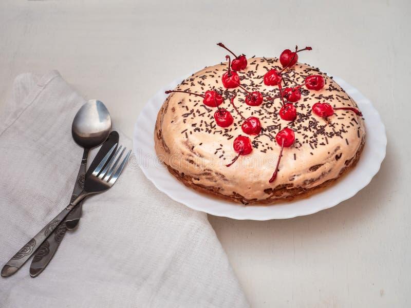 Il dolce casalingo con la crema del acido-cioccolato e cioccolato spruzza e ciliege del cocktail, tovagliolo bianco e bugia della fotografia stock