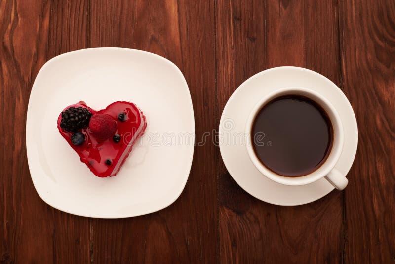 Il dolce e la tazza di caffè saporiti sopra annegano la tavola di legno immagine stock libera da diritti