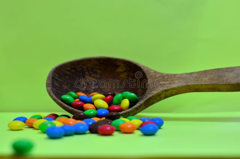 Il dolce ha ordinato il cioccolato multicolore, palle di gomma in un cucchiaio di legno su un fotone verde o compresse e vitamine fotografia stock libera da diritti