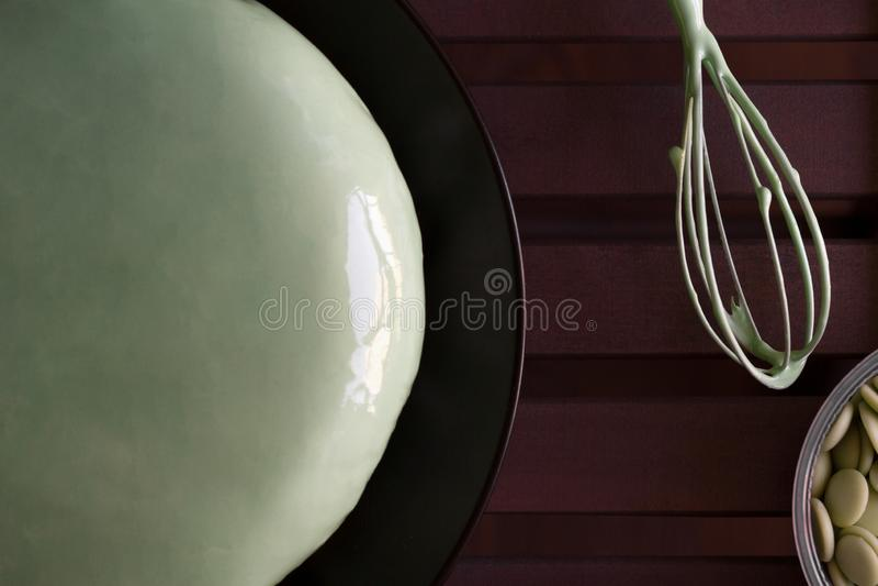 Il dolce verde casalingo della mousse della menta con la glassa dello specchio su una banda nera, un metallo mescolantesi sbatte  immagini stock