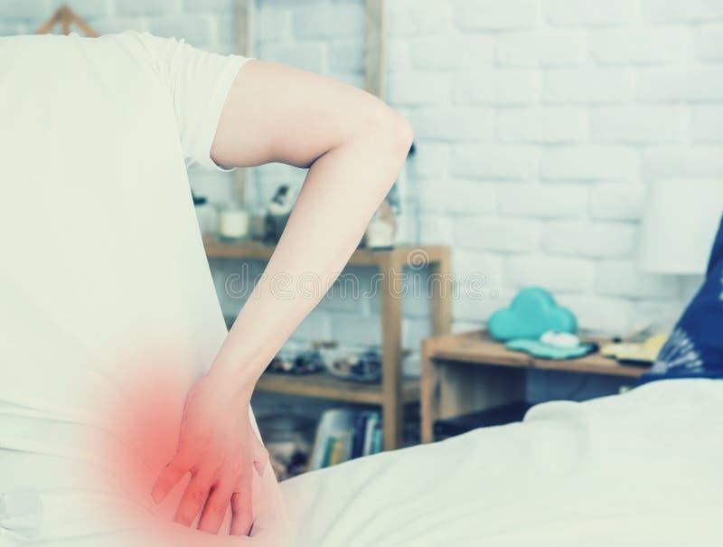 Il dolore alla schiena dell'uomo asiatico e si siede sul letto in camera da letto immagini stock libere da diritti