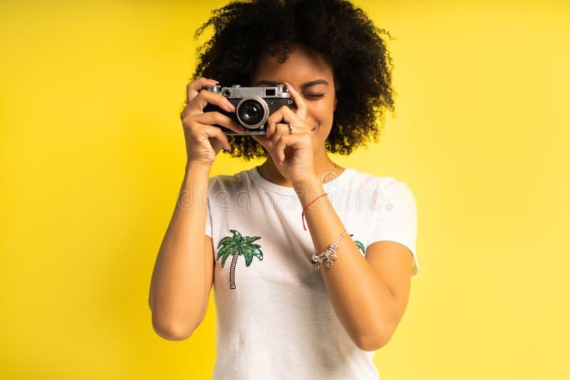 Il donna-fotografo creativo prende le foto, isolate su giallo fotografia stock