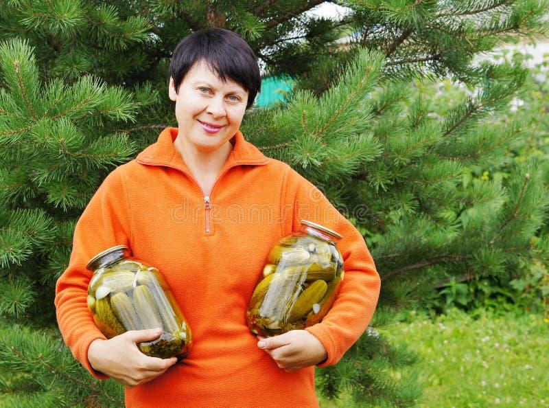 il Donna-giardiniere tiene due vasi con il cetriolo immagini stock