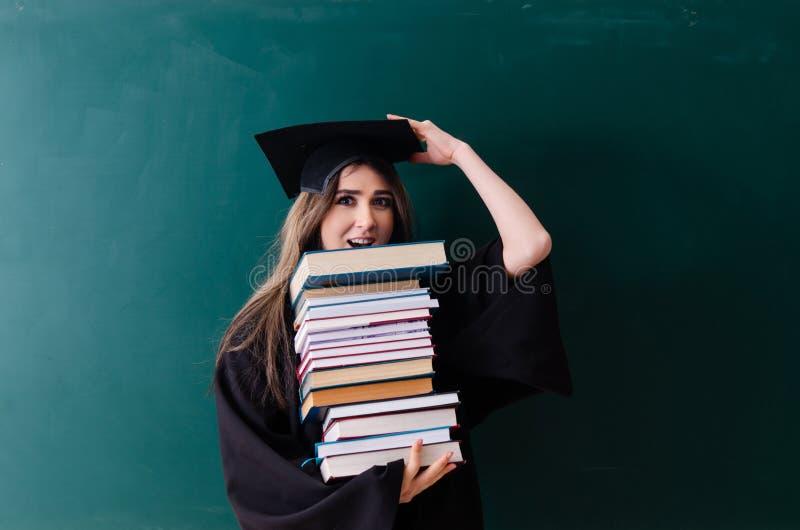 Il dottorando femminile davanti al bordo verde fotografie stock