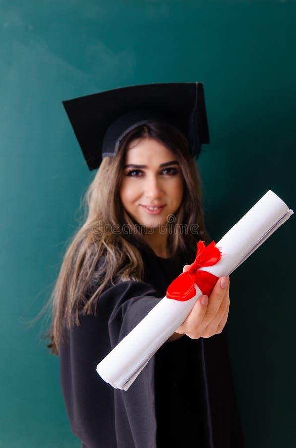 Il dottorando femminile davanti al bordo verde fotografia stock