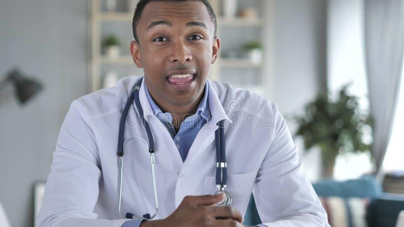 Il dottore afroamericano Talking con il paziente, video chiacchierata immagini stock