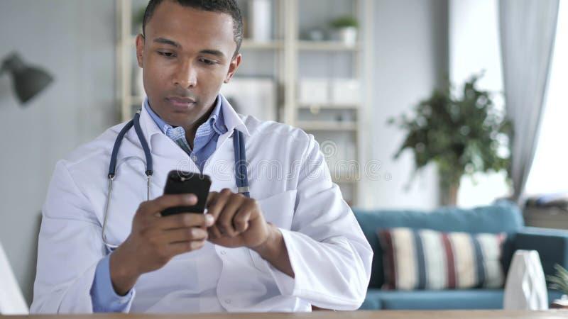 Il dottore afroamericano Using Smartphone fotografia stock libera da diritti