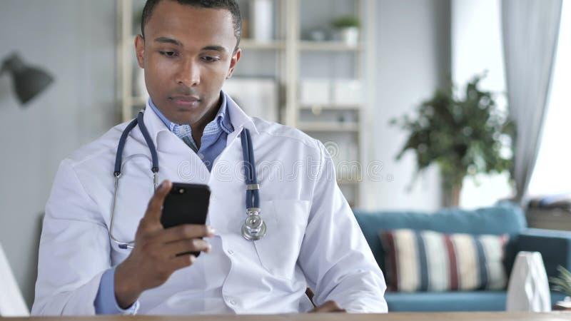 Il dottore afroamericano Using Smartphone fotografie stock libere da diritti