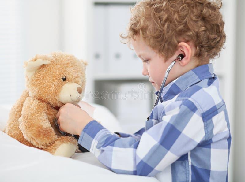 Il dottore Checking del bambino il battito cardiaco di un orsacchiotto fotografie stock