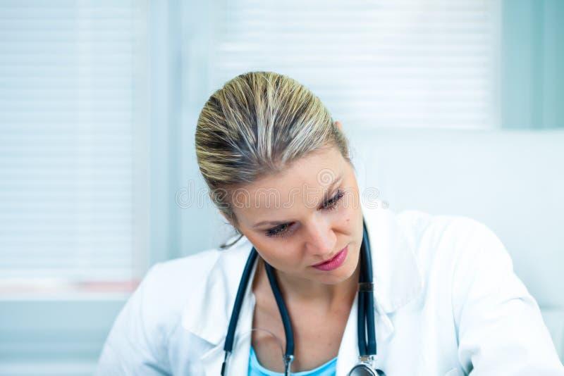 Il dottore Is Concerned femminile abbastanza giovane circa i risultati medici dentro immagini stock