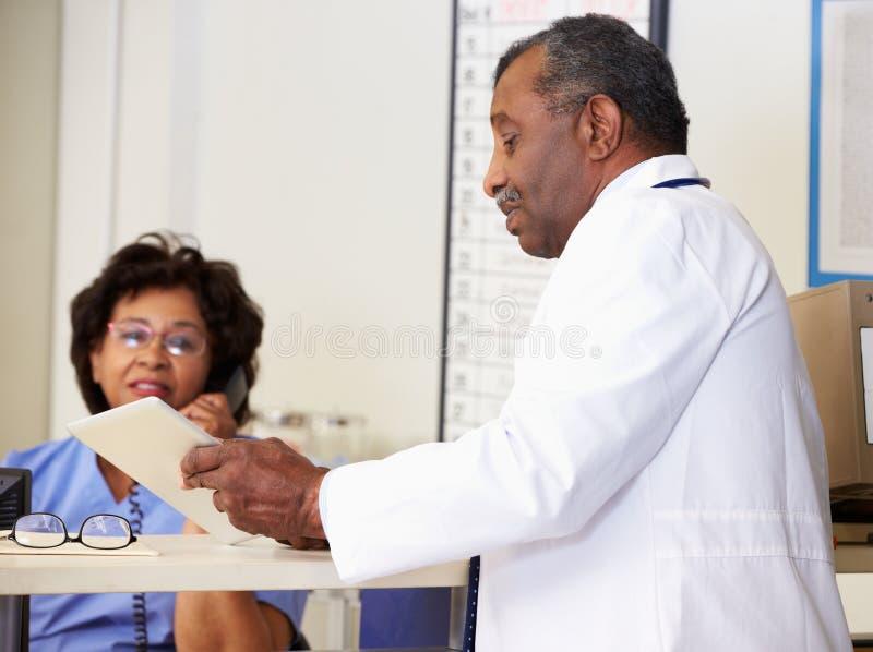 Il dottore In Discussion With Nurse alla stazione degli infermieri fotografia stock libera da diritti