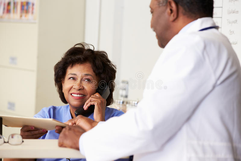 Il dottore In Discussion With Nurse alla stazione degli infermieri fotografie stock