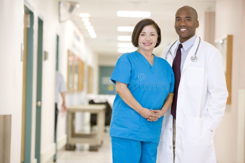 Il dottore ed infermiera che si levano in piedi in un corridoio dell'ospedale immagine stock