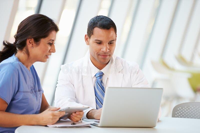Il dottore ed infermiere che hanno riunione informale nella mensa dell'ospedale immagine stock libera da diritti