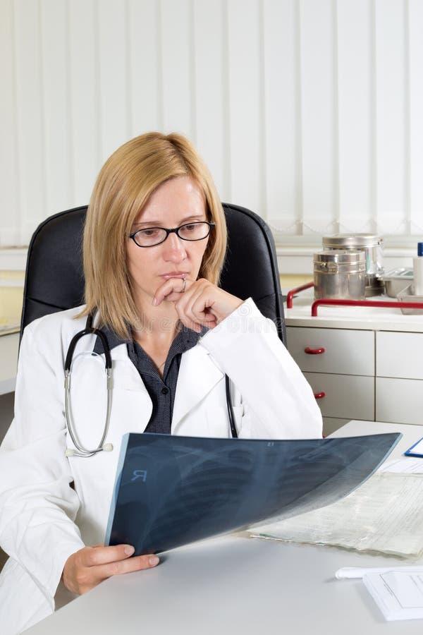 Il dottore femminile preoccupato Examining X-ray di un paziente nella stanza di consulto fotografie stock
