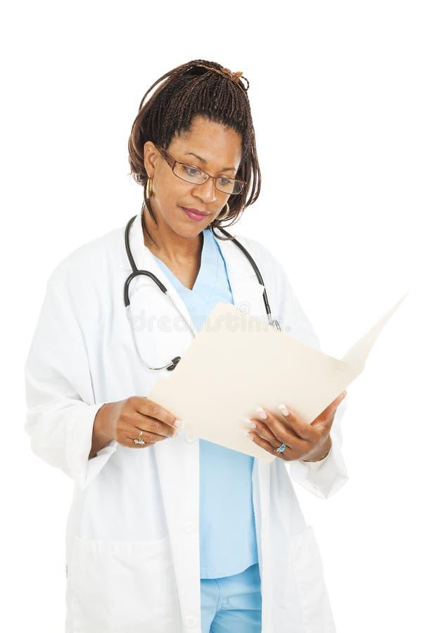 Il dottore grazioso Reads Medical Chart fotografie stock