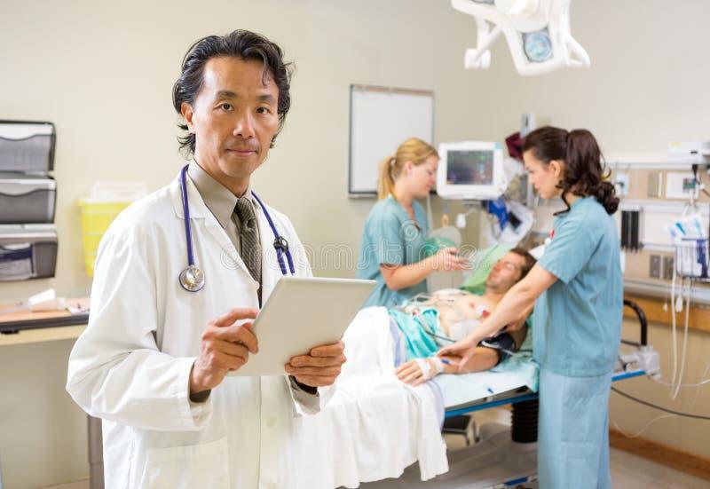 Il dottore Holding Digital Tablet mentre infermieri fotografie stock libere da diritti