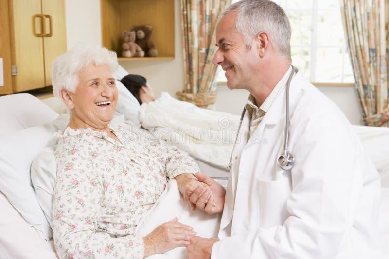 Il dottore Laughing With Senior Woman in ospedale immagini stock libere da diritti