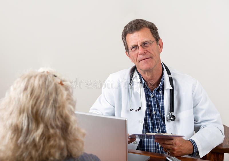 Il dottore Listening al paziente femminile in ufficio immagini stock libere da diritti
