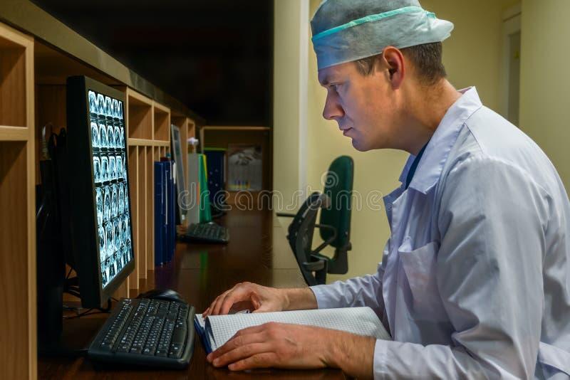 Il dottore Looking al monitor in servizio il servizio notturno immagine stock