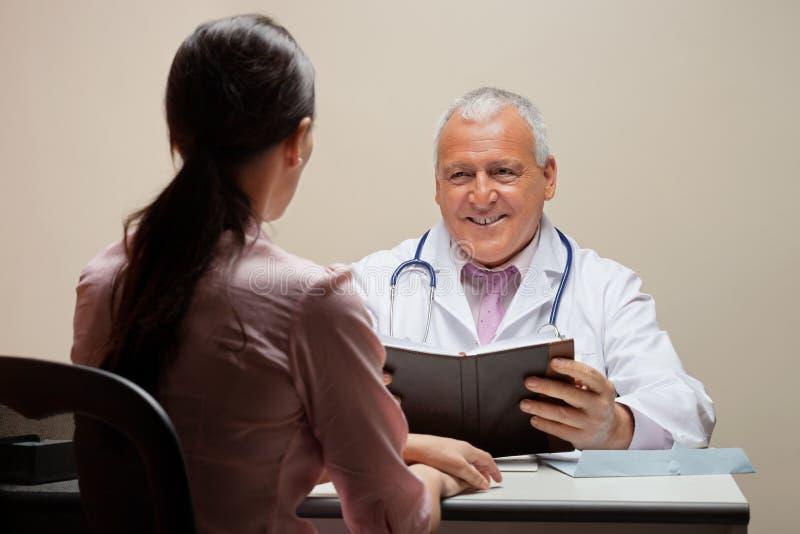 Il dottore Looking At Patient fotografia stock libera da diritti