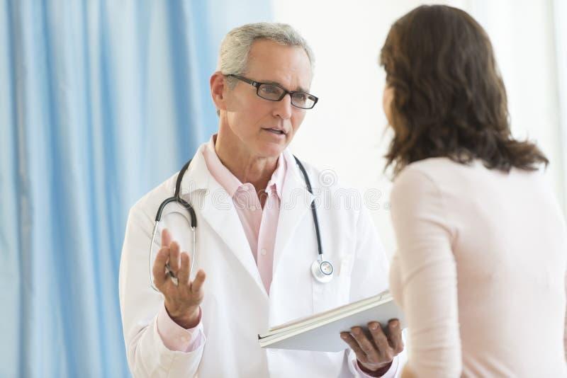 Il dottore maschio Discussing With Patient in clinica immagine stock libera da diritti