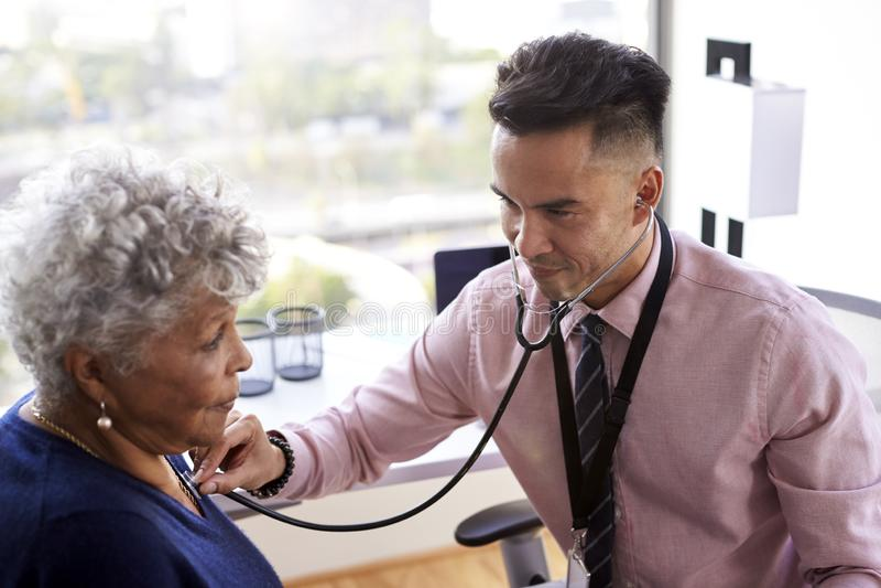 Il dottore maschio In Office Listening al petto femminile senior dei pazienti facendo uso dello stetoscopio immagini stock libere da diritti