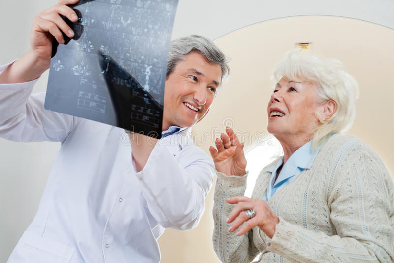 Il dottore With Patient Looking ai raggi x fotografie stock libere da diritti