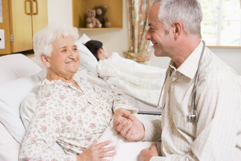 Il dottore Sitting With Senior Woman in ospedale fotografie stock libere da diritti
