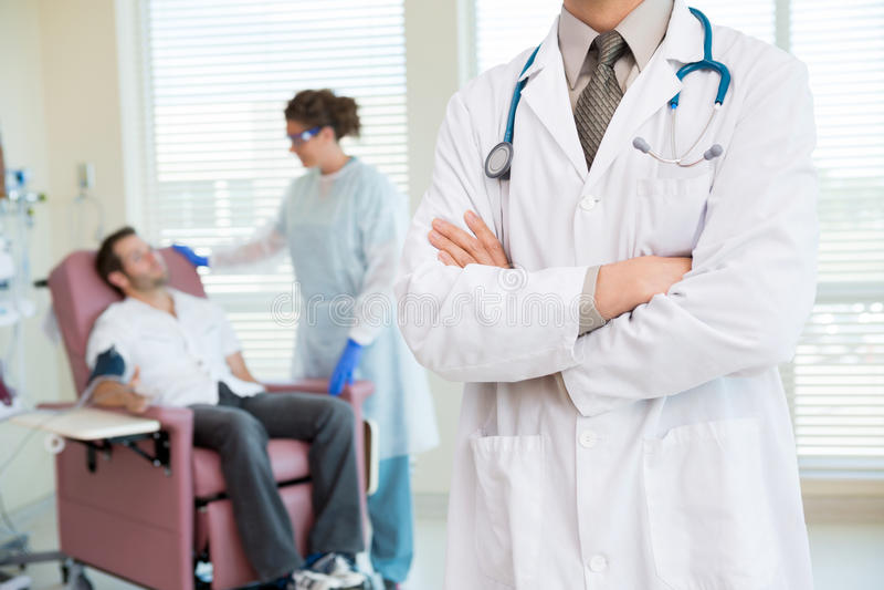 Il dottore Standing Arms Crossed in Chemo Room fotografia stock libera da diritti