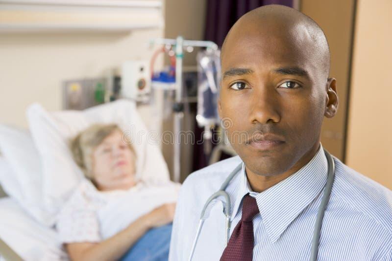 Il dottore Standing In Patients Room immagini stock libere da diritti