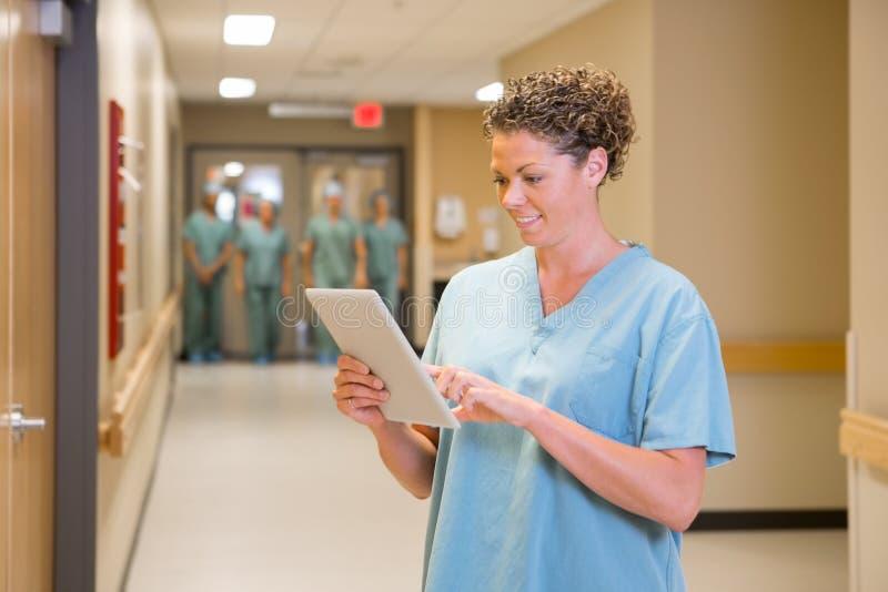 Il dottore Using Digital Tablet in corridoio dell'ospedale immagine stock