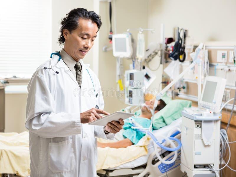 Il dottore Using Digital Tablet mentre riposo paziente fotografia stock libera da diritti