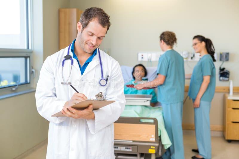 Il dottore Writing On Clipboard con gli infermieri e immagini stock libere da diritti