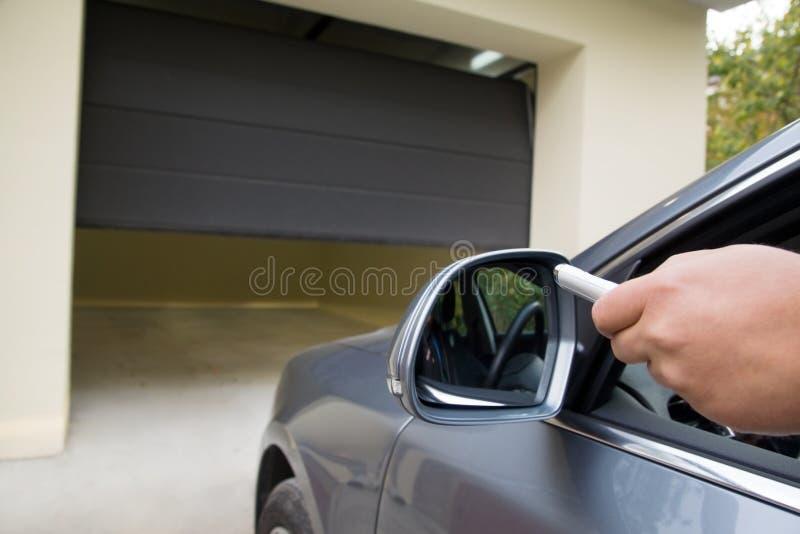 Il driver apre il garage con telecomando immagine stock