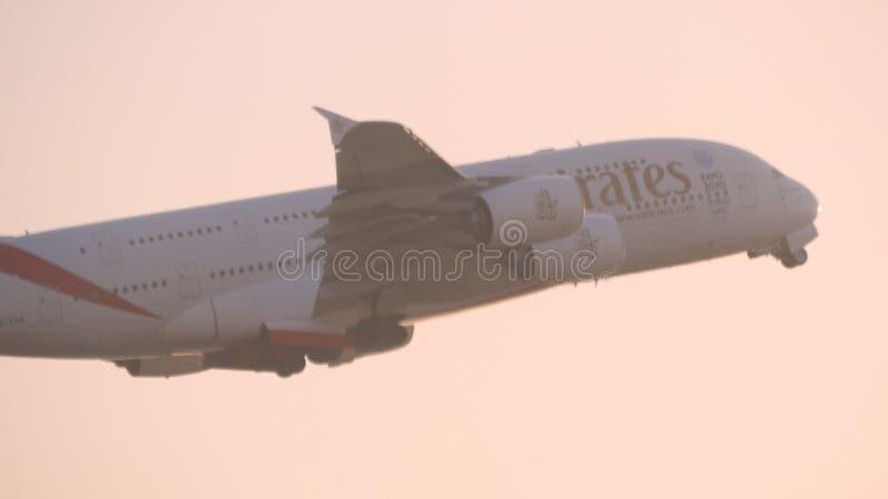 IL DUBAI, EMIRATI ARABI UNITI - 10 MARZO 2017: L'aeroplano del passeggero vola attraverso cielo blu Ltaking piano fuori Velivoli immagini stock libere da diritti