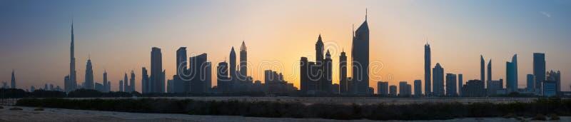 Il Dubai - la siluetta di sera e l'orizzonte della città fotografia stock libera da diritti