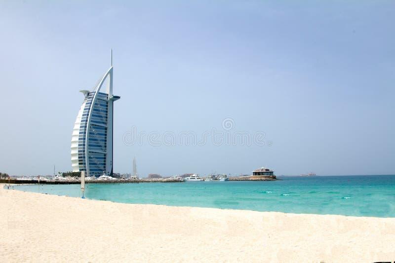 IL DUBAI, UAE - 16 APRILE 2012: Un colpo pulito della spiaggia di Jumeirah con l'hotel di Burj Al Arab nei precedenti immagini stock