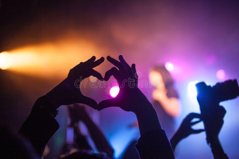 ? il eart, la gente mostra il loro amore, mani sollevate su sul concerto musicale immagini stock