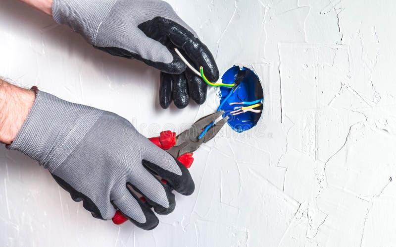 Il electrician& x27; le mani di s con pasatises puliscono i cavi in una scatola di giunzione immagini stock libere da diritti