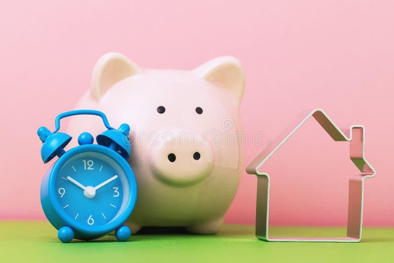 Il est temps d'économiser pour l'immobilier Horloge d'alarme, tirelire et objet en forme de maison image libre de droits