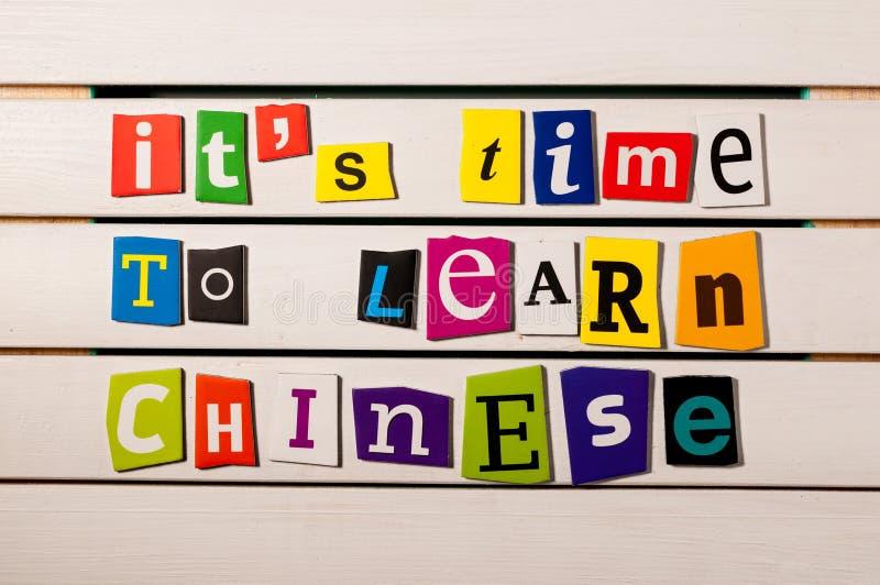 Il est temps d'apprendre le chinois - écrit avec des coupures de lettre de magazine de couleur sur le conseil en bois Connaissanc photo libre de droits