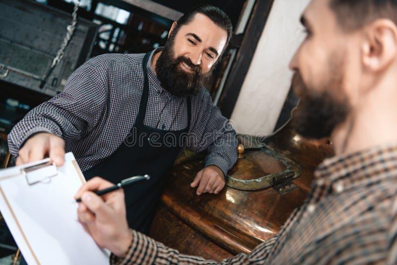 Il fabbricante di birra barbuto contento in grembiule dà i documenti per l'uomo di firma in camicia in fabbrica di birra fotografia stock libera da diritti
