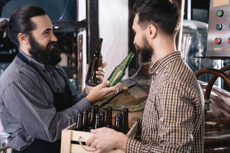 Il fabbricante di birra barbuto prende la bottiglia di birra di vetro di colore in fabbrica di birra Processo di fabbricazione de immagini stock