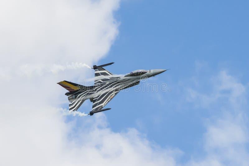 Il falco belga di combattimento F-16 con fumo e condensa la corrente fotografia stock libera da diritti