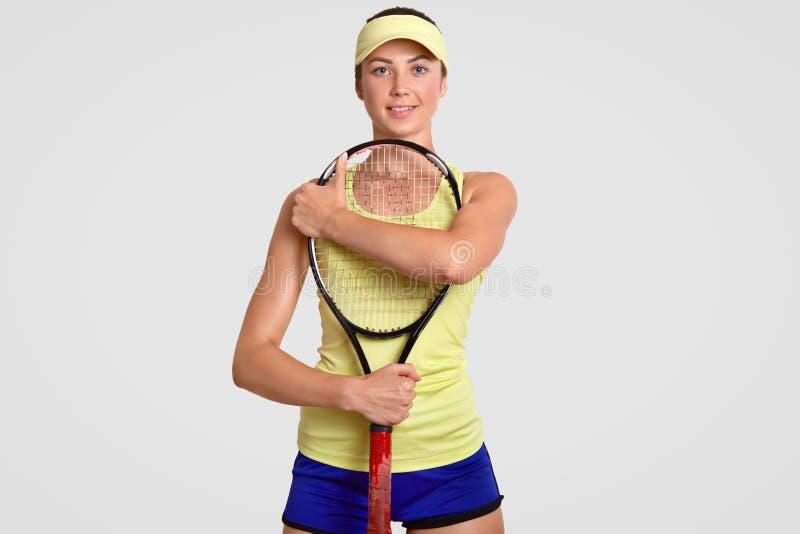 Il fan di tennis femminile sicuro, racchetta di abbracci, ha vestito in tribunale il cappuccio, maglietta e gli shorts, supporti  immagini stock libere da diritti
