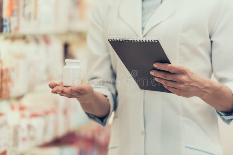Il farmacista del primo piano tiene la bottiglia ed il taccuino di pillole immagine stock libera da diritti
