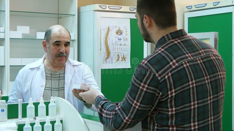 Il farmacista senior ed il giovane cliente maschio hanno conflitto in farmacia immagine stock