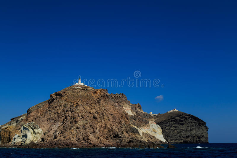 Il faro di Akrotiri in Santorini ha circondato dal mare fotografia stock libera da diritti